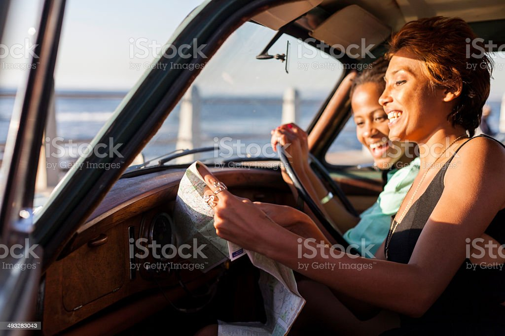 Two female african hipsters sitting in the car, reading the map with...