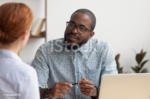 African hr manager listening to caucasian female applicant asking questions at job interview business meeting, diverse recruiter employer and seeker client talking, human resource, recruiting concept