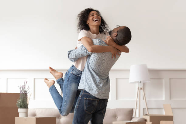 african husband lifting happy wife celebrating moving day with boxes - future hug imagens e fotografias de stock