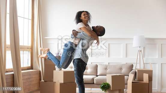 African husband lifting up beloved wife happy family celebrating relocation day full length view, stack of carton boxes on background, moving at new home, property owners, lease loan mortgage concept