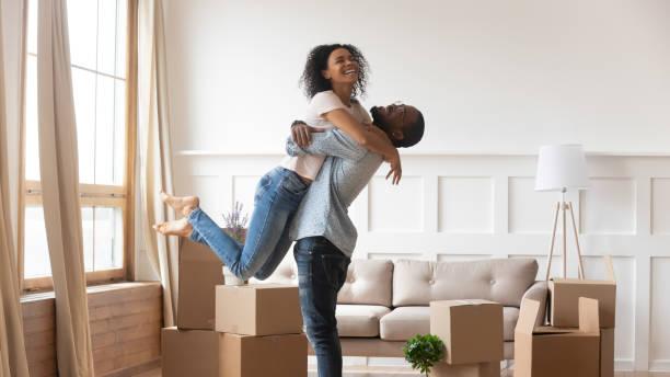 afrikanische ehemann hebt frau glückliche familie feiert umzug tag - eigenheim stock-fotos und bilder