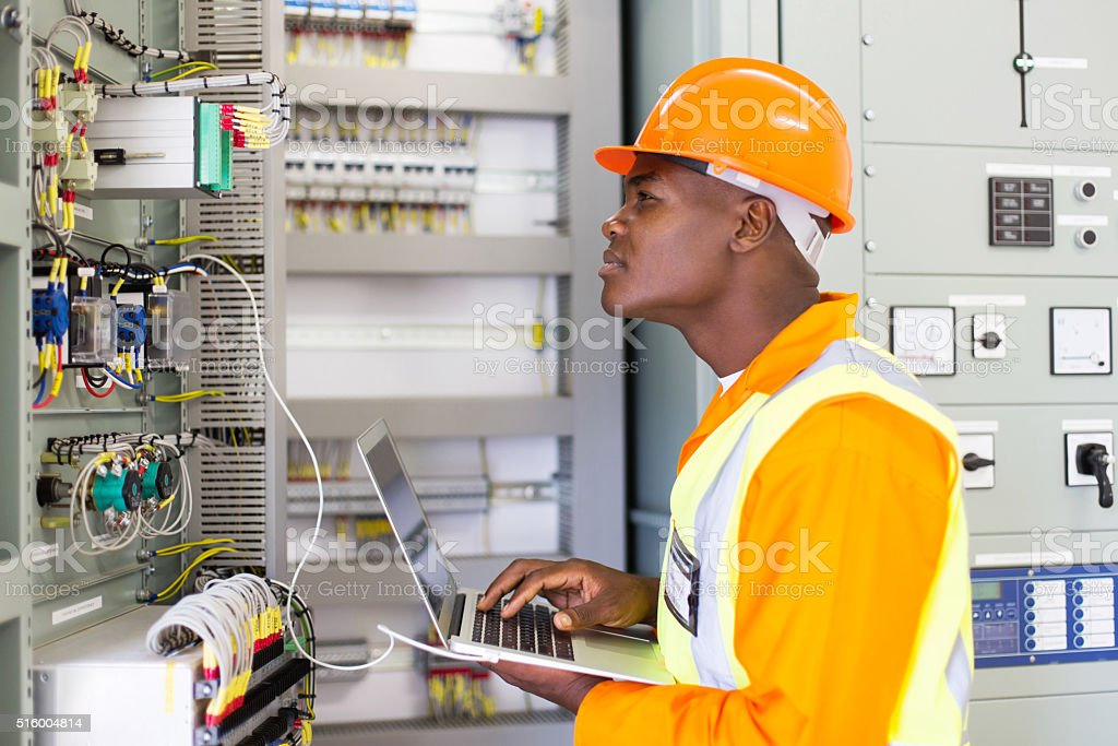 african industrial electrician working in control room stock photo
