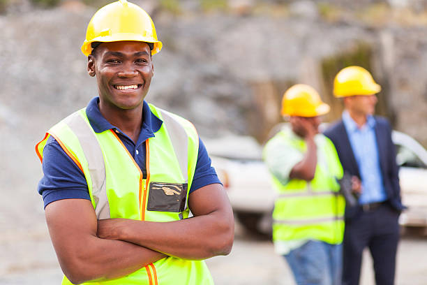 african industrial worker with arms folded stock photo