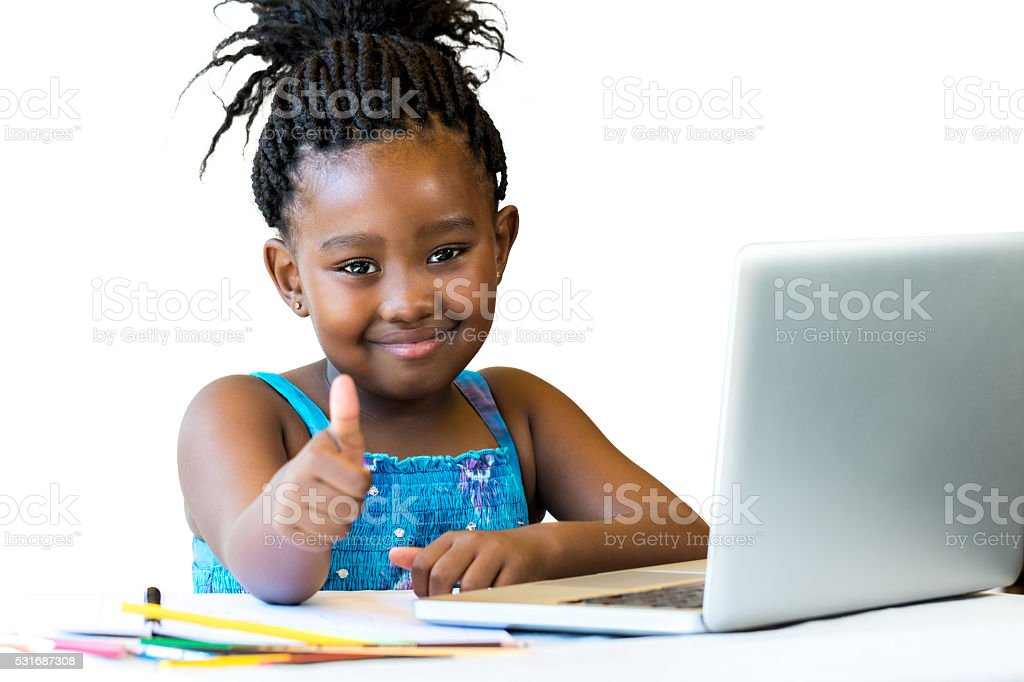 African kid doing thumbs up at desk isolated. stock photo