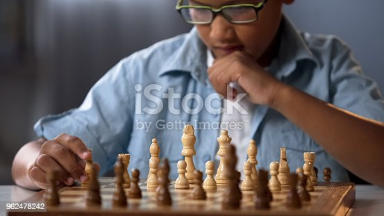 African kid moving knight piece during chess tournament, game strategy analysis