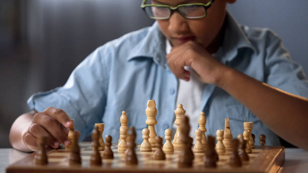 african kid moving knight piece during chess tournament, game strategy analysis - xadrez imagens e fotografias de stock