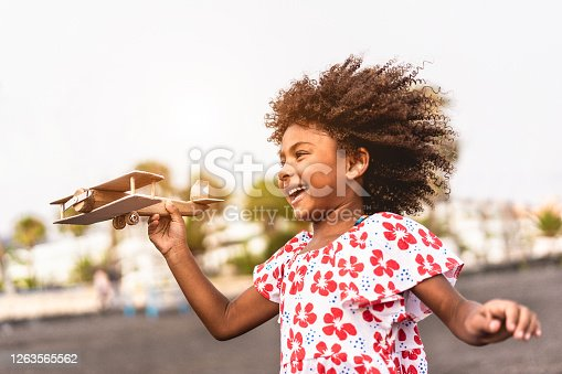 African kid running on the beach while playing with wood toy airplane at sunset, Travel and youth lifestyle concept - Main focus on hand holding plane