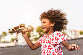 istock African kid running on the beach while playing with wood toy airplane at sunset, Travel and youth lifestyle concept - Main focus on hand holding plane 1263565562