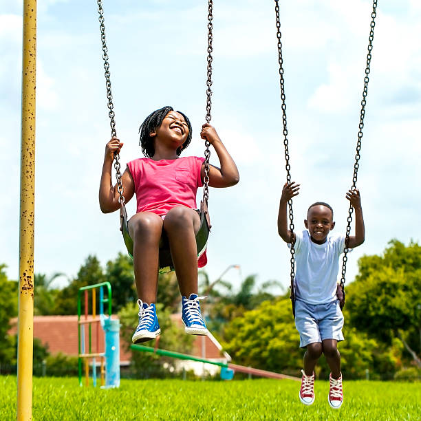 African kids having fun swinging in park. stock photo