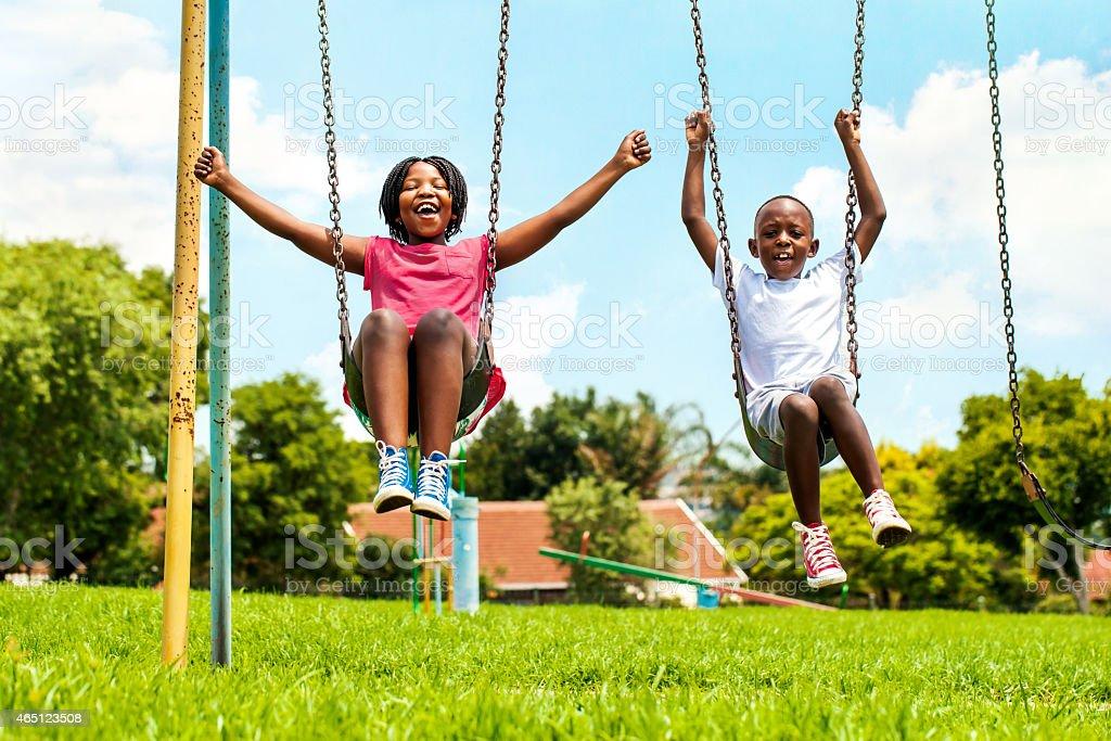 African kids playing on swing in neighborhood. stock photo