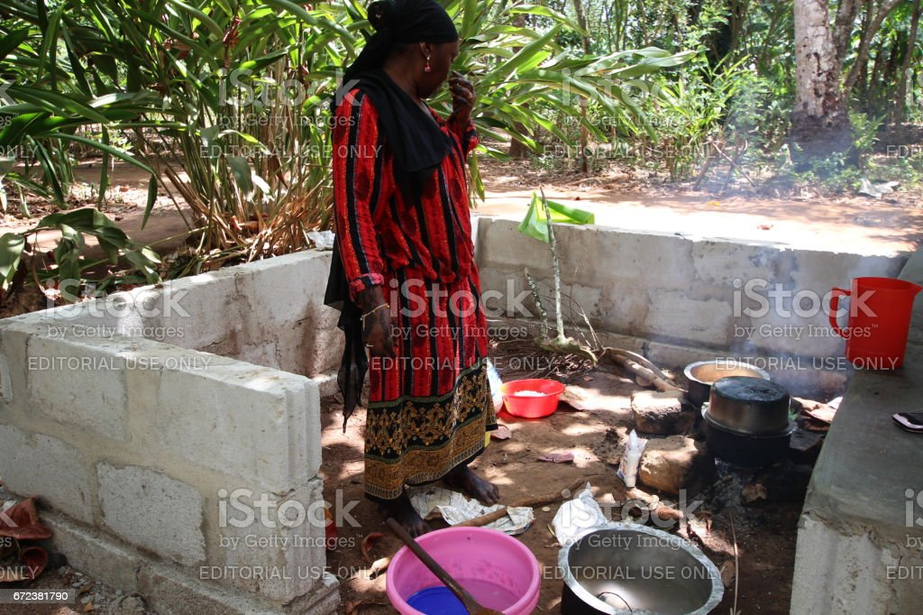 African Lady cooks at fireplace in Zanzibar, Tanzania, Indian Ocean, East Africa stock photo