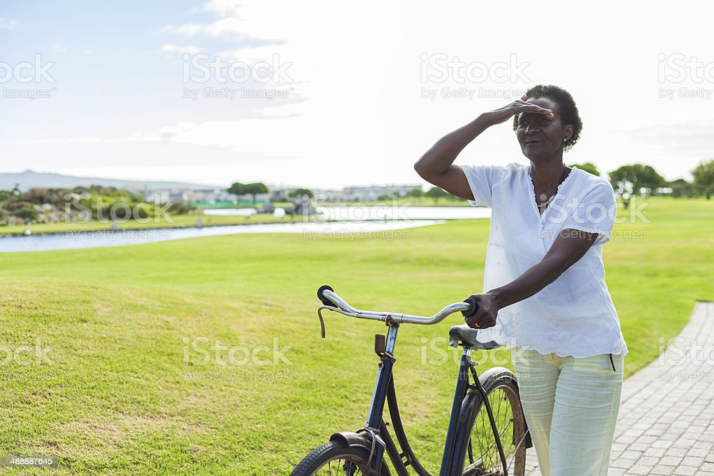 African lady with a bike on a golf course stock photo