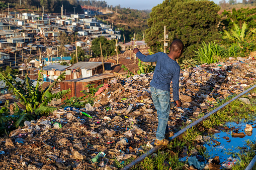 African little boy walking on railroad tracks, Kibera slum on the background, Kenya, East Africa. Kibera is the largest slum in Nairobi, the largest urban slum in Africa, and the third largest in the world