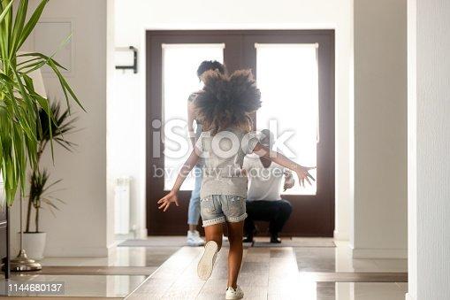 istock African little daughter running to parents who standing in doorway 1144680137
