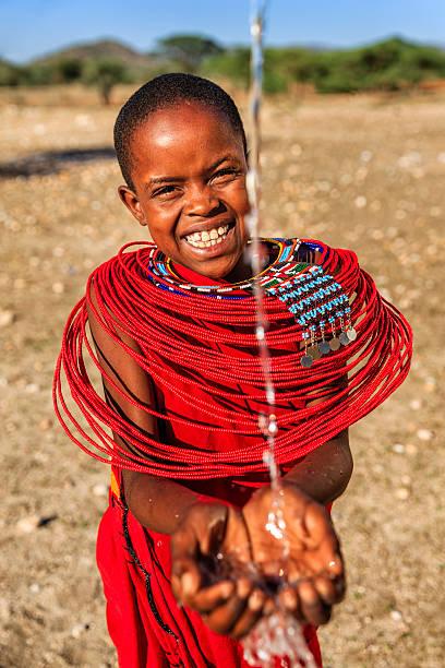 African little girl drinking fresh water on savanna, East Africa stock photo