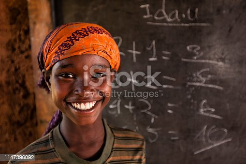 African little girl during math class class in very remote school. The bricks that make up the walls of the school are made of clay and straw. There is no light and electricity inside the classroom
