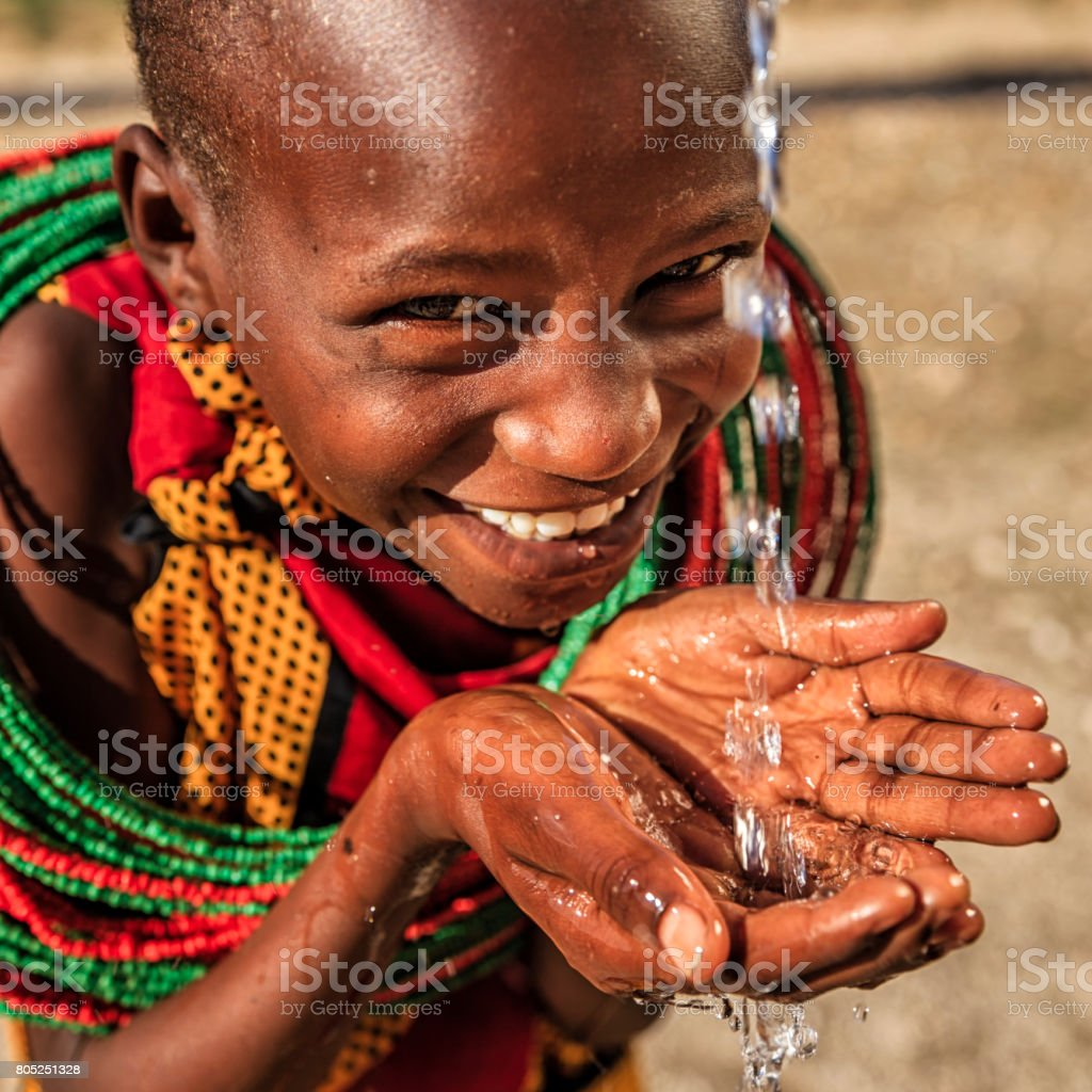 African little girl from Samburu tribe drinking fresh water on savanna., East Africa stock photo