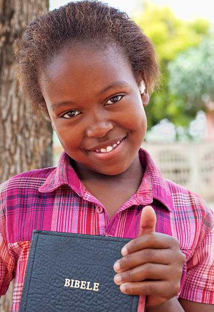 African Little Girl holding a bible stock photo