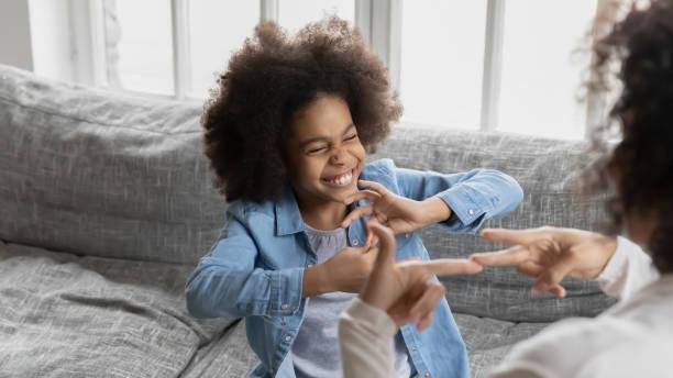 afrikaans meisje dat gebarentaal gebruikt communiceert met mamma - doofheid stockfoto's en -beelden