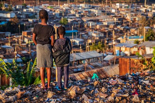 African little girls standing in trash and looking at houses in Kibera slum, Kenya, East Africa. Kibera is the largest slum in Nairobi, the largest urban slum in Africa, and the third largest in the world