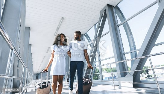 istock African Lovers travel, loving couple walking at airport with suitcases 1165261091
