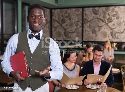 istock African male administrator welcoming restaurant guests 1081328870