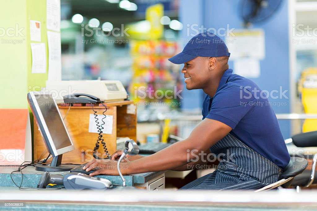 african male cashier working at till point stock photo