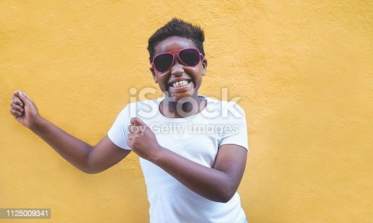 African male child dancing outdoor wearing sunglasses - Black afro kid having fun with yellow background - Focus on face - Youth lifestyle, trendy , fashion and happiness concept