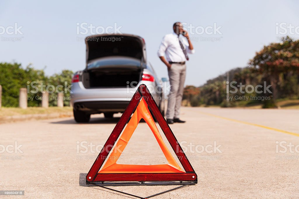 african male driver calling for help after car broke-down stock photo