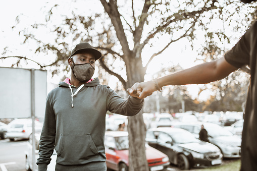 African Male Friends Making Fist Bump And Maintaining Social Distancing During Pandemic
