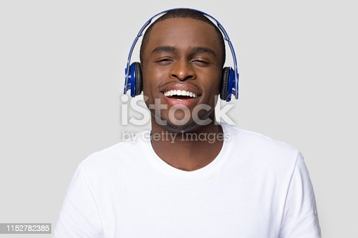 African man wearing headphones wireless device listen favourite songs music via bluetooth feels happy enjoy modern track pose isolated studio shot on grey blank, free time, hobby and lifestyle concept