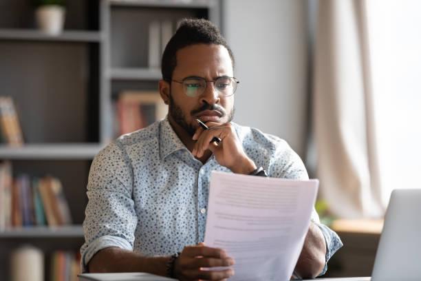 африканский мужчина адвокат читать детали контракта чувствует недовольство концепции - письмо документ стоковые фото и изображения