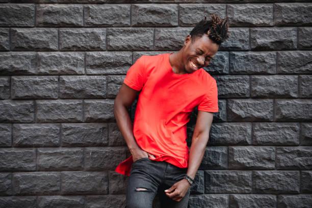 afrikanische männermodel in leeren roten t-shirt lachen gegen mauer - rote dreads stock-fotos und bilder
