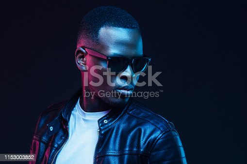 1095939686istockphoto African male model neon portrait, wearing trendy sunglasses and leather jacket. Copy space for your text 1153003852