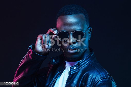 1095939686istockphoto African male model portrait with serious face, wearing trendy sunglasses and leather jacket 1153003840