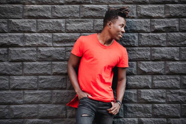 afrikanische männermodel stehend in leeren roten t-shirt gegen mauer - rote dreads stock-fotos und bilder