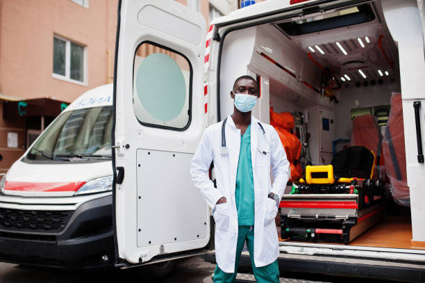 African male paramedic standing in front of ambulance car. stock photo