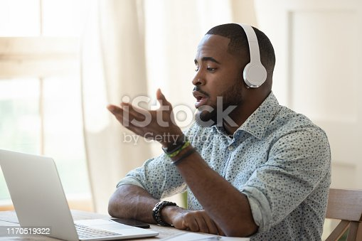 Serious african male interpreter skype teacher wearing headphones looking at laptop talking by online chat, black man tutor teaching student learning in internet video calling on computer sit at desk