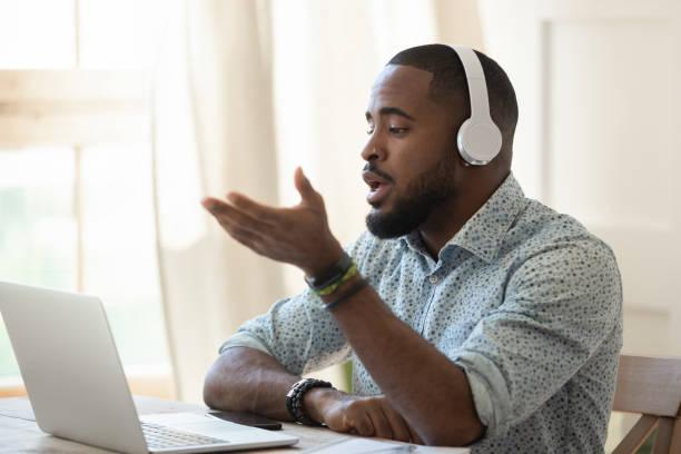 african male skype teacher wearing headphones talking looking at laptop - skype imagens e fotografias de stock