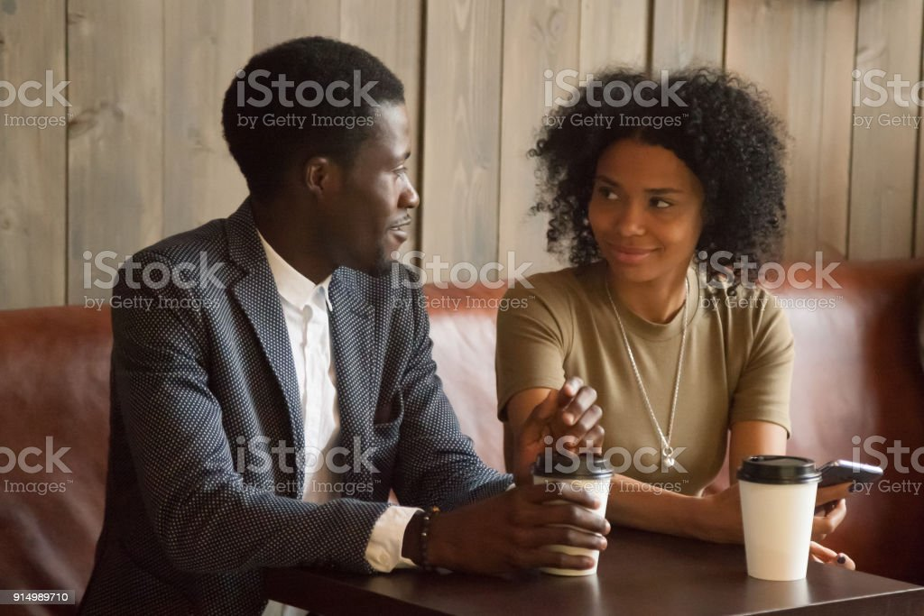 African man and woman talking flirting sitting at coffeehouse table stock photo