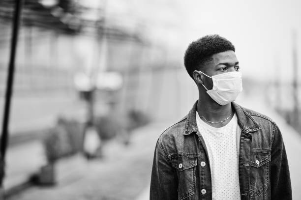 African man at park wearing medical masks protect from infections and diseases coronavirus virus quarantine. stock photo