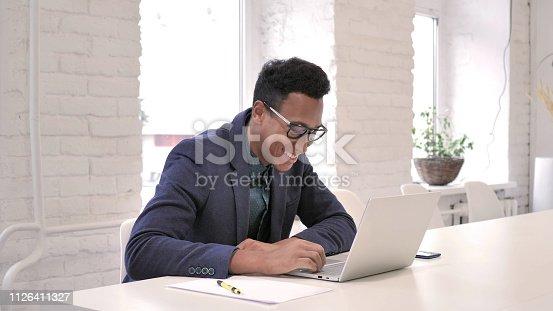 888751614 istock photo African Man Celebrating Success, Working on Laptop 1126411327