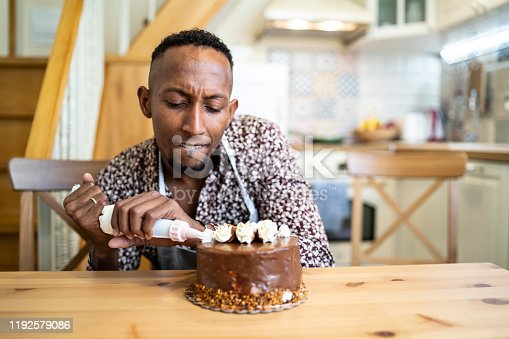 istock African man decorating birthday cake at home, making faces 1192579086