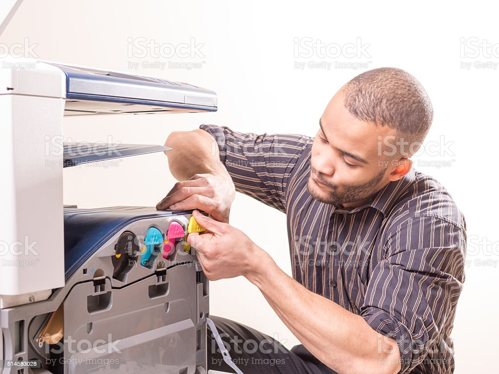 african man fixing photo copier stock photo