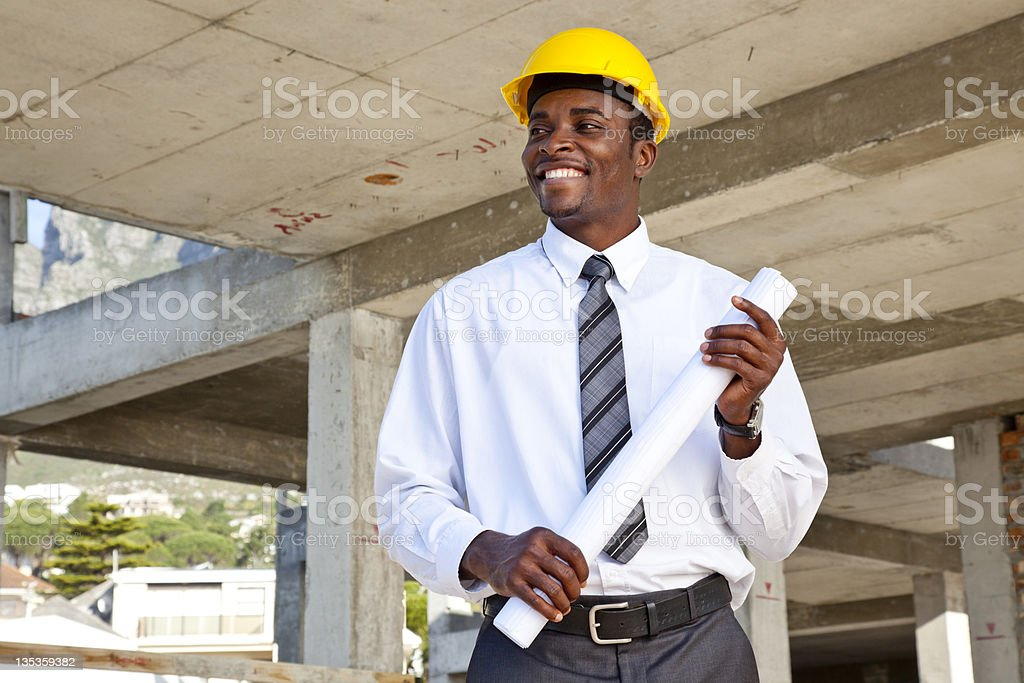 African man holding architectural plans stock photo