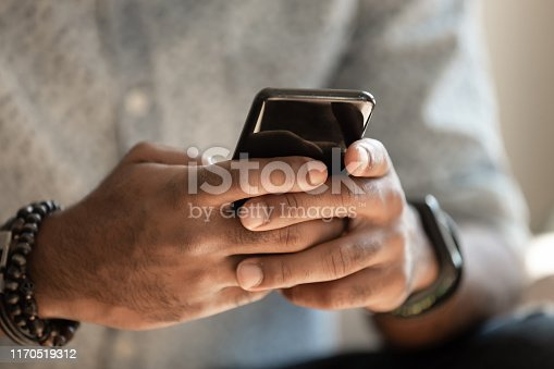 African american man using cellphone applications texting message in messengers, male black hands holding phone working playing game on smartphone, mobile technology lifestyle concept, close up view