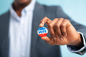 African man holding vote button on blue background for the November elections in the United States 2020, blurred