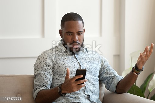 502723248 istock photo African man holds cellphone read sms feels shocked 1217477771
