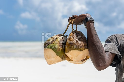 African man holds fresh coconuts for tourist on the sand beach, Zanzibar, Tanzania, close up of Zanzibar island, Tanzania, East Africa, close up