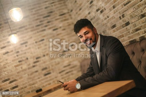istock African man in a bar using phone 625722174